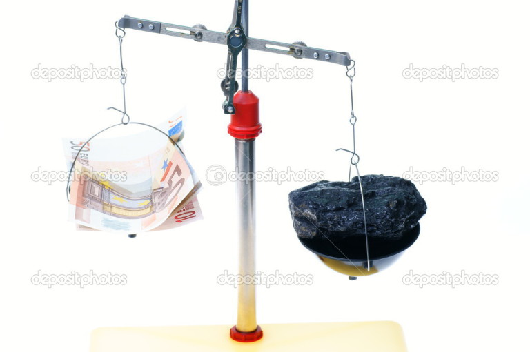 scale pan with money and coal
